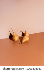 Pears leaning against brown colored walls with harsh sunlight.