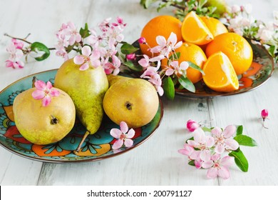 pears and oranges in the plates on the table