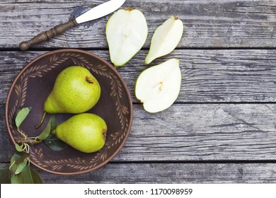 pears in a plate and slices of pears top view. wooden background with pears. ripe organic pears close-up.