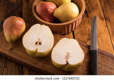 Pears sliced on a wooden board in window light photographed in a dark food style
