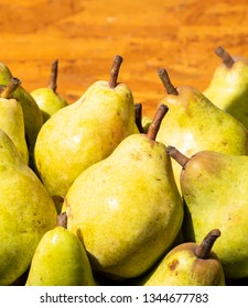 Pears in sun light rays in wooden box at stall of local organic farmer market in Paris, France.