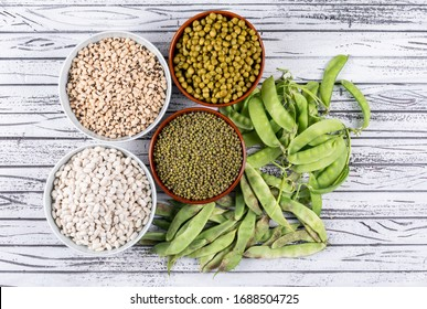 Peas and beans in bowls some of them around flat lay on a gray wooden background