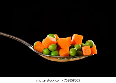 peas and carrots on a spoon
