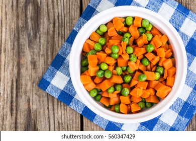 Peas and carrots in a white salad bowl, view from above on a wooden background. Studio Photo