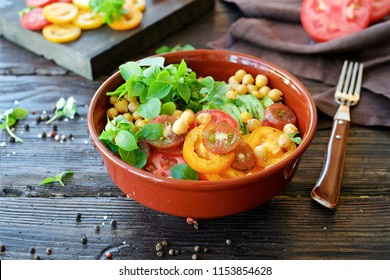 Сhick peas salad bowl with tomatoes, basil and avocado. Brown wooden background.Closeup view