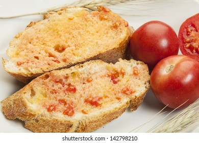 Peasant bread  with tomato rubbed over and seasoned with olive oil and salt/ Mediterranean diet. Bread with tomato and olive oil
