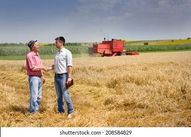 Peasant and businessman shaking hands on wheat field