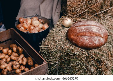 Peasant food in farmer style: baked bread, onions, potatoes on bales of hay. Concept Old Russian rustic style.