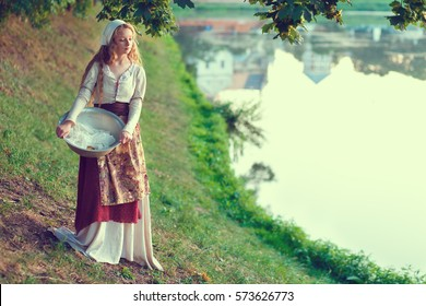 Peasant Girl.  A peasant woman washes clothes in the river