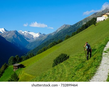 Peasant with scythe in front of mountain landscape