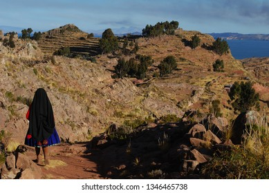 Peasant from Taquile Island walks through the fields surrounded by the waters of Lake Titicaca in Puno.