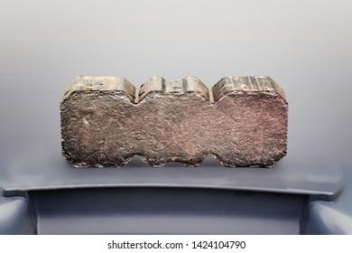 Peat briquette on a grey plastic box. Close up.