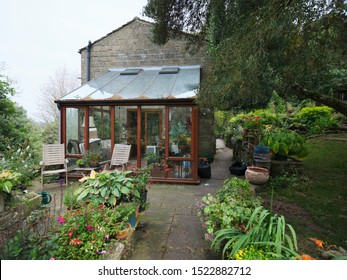 Peat Lane, Bewerley, North Yorkshire, England, UK. 18/09/19 In the small holding amateur garden, autumn colours begin to surround a conservatory on a traditional cottage. Nidderdale at 900ft