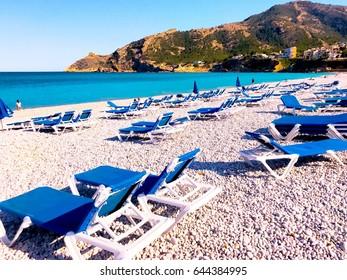 Pebble beach in Albir (Spain). Beach chairs  on Spanish coast.