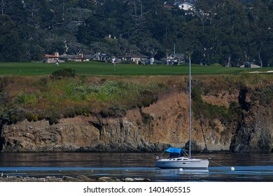 PEBBLE BEACH, CALIFORNIA - JULY 7, 2018: A sailboat moored along the 18th hole of Pebble Beach Golf Links in Pebble Beach, California, as viewed from a viewpoint near the 18th green.