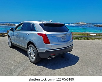PEBBLE BEACH, CALIFORNIA/USA - JULY 8, 2018: A 2018 Cadillac XT5 parked along the scenic 17-Mile Drive. The 17-Mile Drive gates are open from sunrise to sunset and are marked by red-dashed line marks.