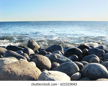 Pebble beach near Larvik in Norway. Sky and sea are united in a clear line on the horizon.