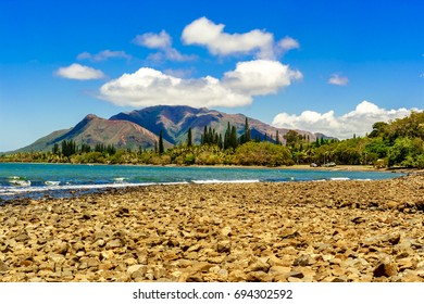 pebble beach in new Caledonia with mountains