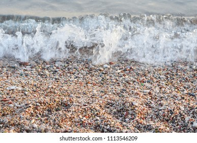 Pebble beach and sea wave at the sunset