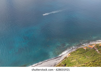 Pebble beach seen from a high point with a few houses, banana plantation and a boat traveling in the ocean