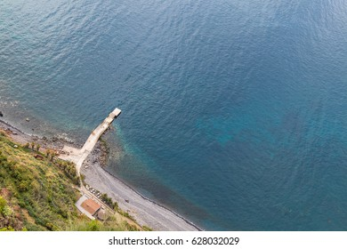 Pebble beach seen from a high point with a small pier into the clear blue ocean