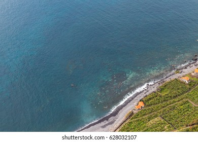 Pebble beach seen from a high point with many houses and banana plantations just in front of clear water ocean