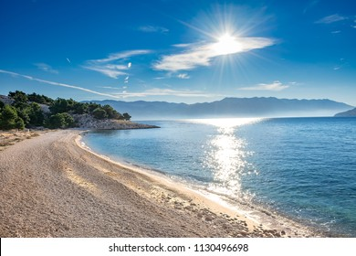 Pebble beach and sunburst in the blue sky. Baška, Island of Krk, Croatia