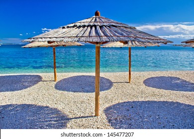 Pebble beach and turquoise sea umbrella, Zrce beach, Island of Pag, Croatia