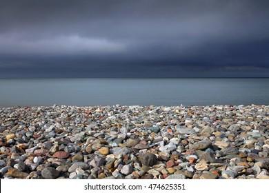 Pebble covered beach and a stormy sky at Llandudno, North Wales.