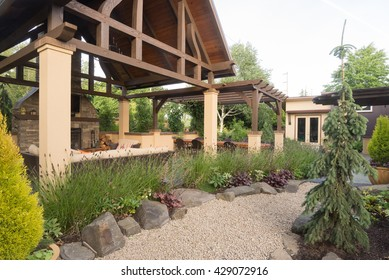 A pebble pathway winds past a custom-designed backyard patio shelter.
