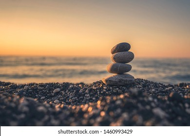 A pebble pyramid on a beach in the sunrise/sunset