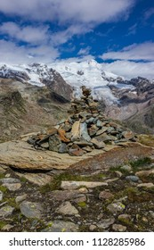 Pebble stack to indicate the path at Colle della Bettaforca (Monte Rosa Massif, Aosta Valley, Italy). In the background, Vincentpiramid (4,215 m - 13,829 ft).