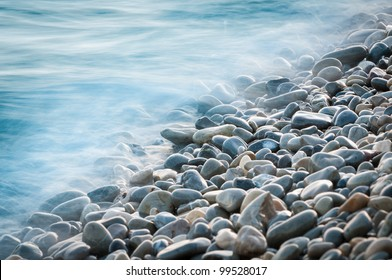 pebble stones by the sea. Silky waves of blue sea from long exposure.