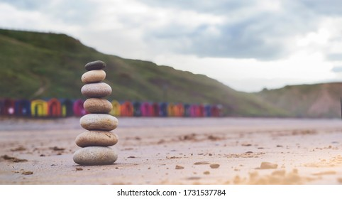 Pebble tower by the seaside with blurry colorful beach ht background,Stack of zen stones on the sand, Stones pyramid on the beach symbolizing, stability, harmony, balance with shallow depth of field.