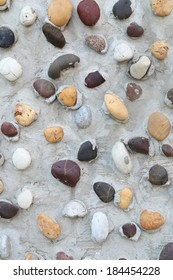 Pebbles in concrete wall texture background