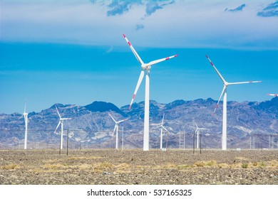 The pebbles on the ground and the wind turbines in front of mountains