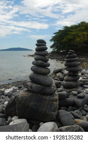 Pebbles are piled on a volcanic rock by the sea. Zen concept. Copy space.