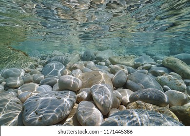 Pebbles and rocks below water surface underwater in the Mediterranean sea, Valencia, Spain