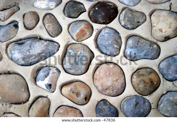 Pebbles set in concrete. Ideal for a background.