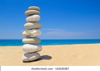 Pebbles stack balance over blue ionian sea in Greece. Blue sky and water on sunny coast in summer.