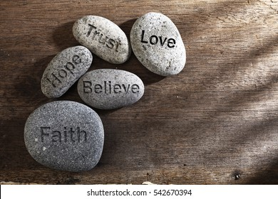 pebbles or stone with inspirational text Faith, trust, believe, hope and love