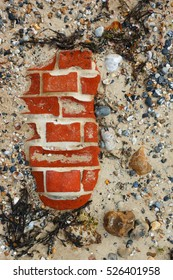Pebbles, stones, shells, seaweed and part of a brick wall on a beach weathered by the wind and waves.