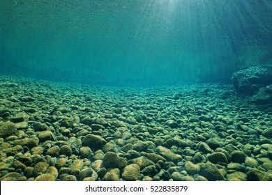Pebbles underwater on riverbed with clear freshwater and sunlight through water surface, natural scene, Dumbea river, New Caledonia, south Pacific