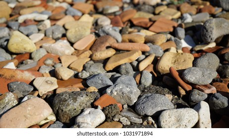 pebbles of various colors on a beach in the sun