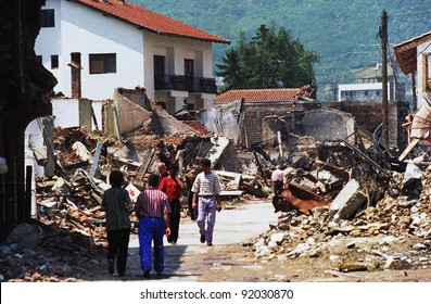 PEC, KOSOVO - JULY 3:Returning  refugees survey the destroyed downtown of Pec, Kosovo, on Saturday, July 3, 1999.  Much of Kosovo was destroyed during fighting with Serb forces.