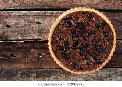 Pecan and cranberry autumn pie on rustic old wood, overhead view