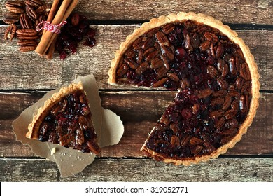Pecan and cranberry autumn pie, overhead table scene with cut slice on rustic wood
