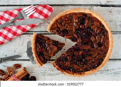 Pecan and cranberry autumn pie, overhead table scene on white wood with slice being removed