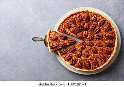 Pecan nut pie, on a plate. Grey background. Copy space. Top view.