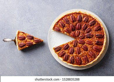 Pecan nut pie, on a plate. Grey background. Close up. Top view.